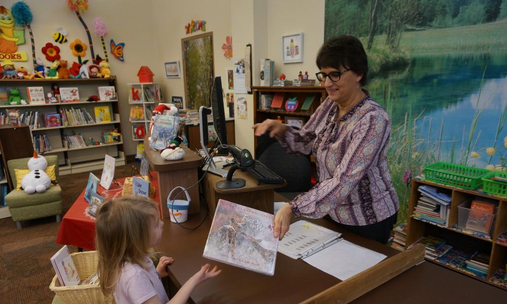 A librarian handing a student a book